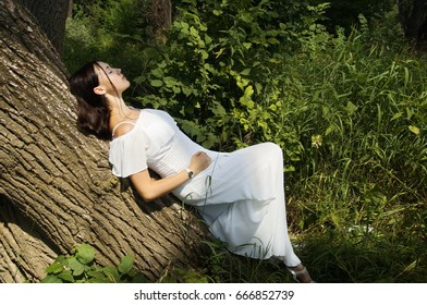 Brunette girl in white light dress barefoot against the backdrop of green forest