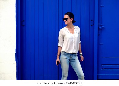 Brunette girl with white shirt and sunglasses on a blue background