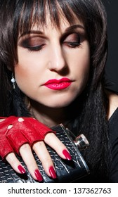 Brunette glam rock style with a flask in hand