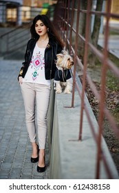 Brunette gypsy girl with yorkshire terrier dog posed against steel railings. Model wear on leather jacket and t-shirt with ornament, pants and shoes with high heels.