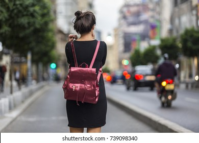 Brunette with hair pinned up wearing a jersey black short dress. Woman on street wearing a metal backpack. Hair style ideas for life on the go. Metallic accessory with long straps. Woman on the go.