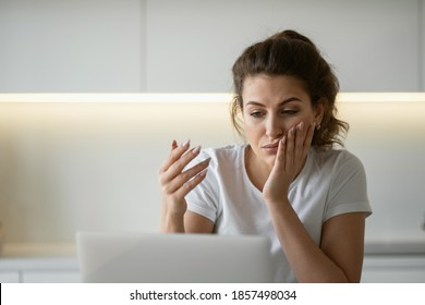 Brunette hair in a ponytail is beautiful in a comfortable white t-shirt. copy space. a woman is sitting at home in the kitchen at a laptop computer doing tasks for work online in quarantine.