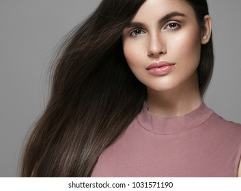 Brunette hair woman. Beautiful brunette hairstyle fashion portrait with beauty long black hair over gray background. Studio shot.