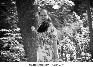 Brunette hair woman middle age in light summer dress rest in central city park. Emotional woman feeling happy and have a good day. Lady plus size figure