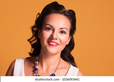 Brunette with hairdo and make up poses in studio, pin up style, close up portrait