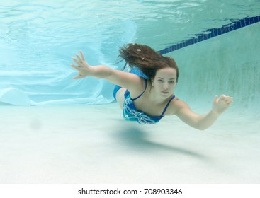 Brunette haired woman in a pool swimming underwater