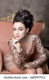 Brunette with hairstyle wearing golden trendy dress posing in armchair/Fashionable woman in stunning dress