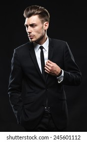 brunette handsome man in a suit on a dark background