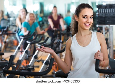 Brunette happy european girl and other females working out in sport club