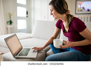 Brunette having good time on the living room with coffee and laptop