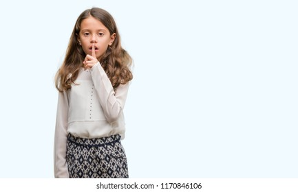 Brunette hispanic girl asking to be quiet with finger on lips. Silence and secret concept.