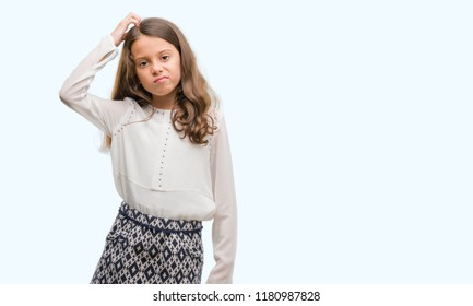 Brunette hispanic girl confuse and wonder about question. Uncertain with doubt, thinking with hand on head. Pensive concept.