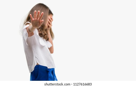 Brunette hispanic girl covering eyes with hands and doing stop gesture with sad and fear expression. Embarrassed and negative concept.