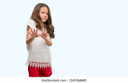 Brunette hispanic girl disgusted expression, displeased and fearful doing disgust face because aversion reaction. With hands raised. Annoying concept.