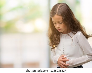 Brunette hispanic girl with hand on stomach because nausea, painful disease feeling unwell. Ache concept.