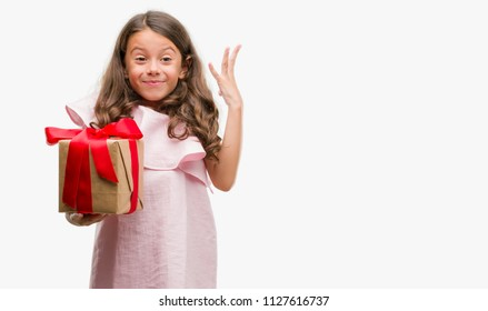 Brunette hispanic girl holding a gift very happy and excited, winner expression celebrating victory screaming with big smile and raised hands