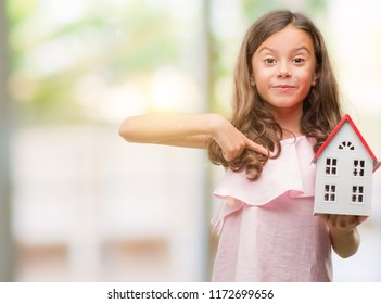 Brunette hispanic girl holding little house with surprise face pointing finger to himself