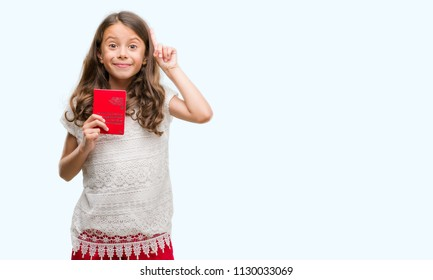 Brunette hispanic girl holding passport of Switzerland surprised with an idea or question pointing finger with happy face, number one