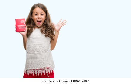 Brunette hispanic girl holding passport of Switzerland very happy and excited, winner expression celebrating victory screaming with big smile and raised hands