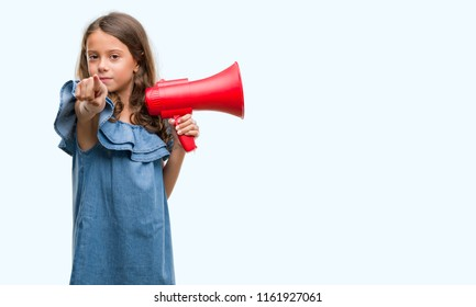Brunette hispanic girl holding red megaphone pointing with finger to the camera and to you, hand sign, positive and confident gesture from the front