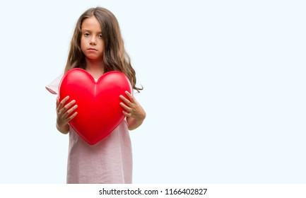 Brunette hispanic girl holding red heart with a confident expression on smart face thinking serious