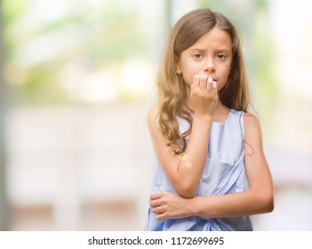 Brunette hispanic girl looking stressed and nervous with hands on mouth biting nails. Anxiety problem.