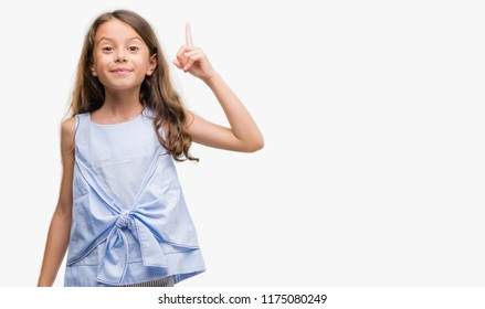 Brunette hispanic girl pointing finger up with successful idea. Exited and happy. Number one.