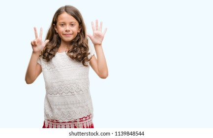 Brunette hispanic girl showing and pointing up with fingers number eight while smiling confident and happy.