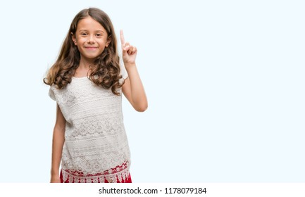 Brunette hispanic girl showing and pointing up with finger number one while smiling confident and happy.