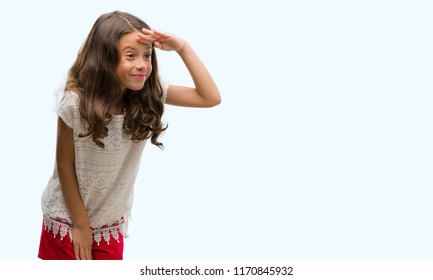 Brunette hispanic girl very happy and smiling looking far away with hand over head. Searching concept.
