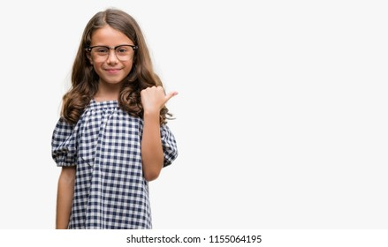 Brunette hispanic girl wearing glasses pointing and showing with thumb up to the side with happy face smiling