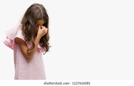 Brunette hispanic girl wearing pink dress tired rubbing nose and eyes feeling fatigue and headache. Stress and frustration concept.