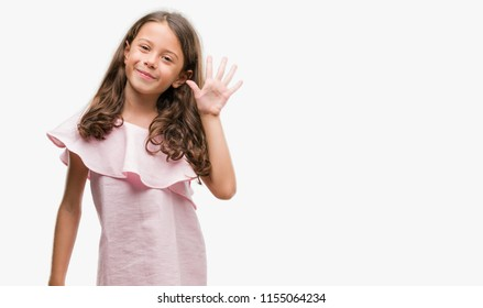 Brunette hispanic girl wearing pink dress showing and pointing up with fingers number five while smiling confident and happy.
