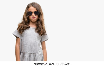 Brunette hispanic girl wearing sunglasses skeptic and nervous, frowning upset because of problem. Negative person.