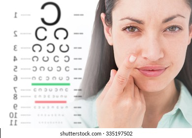 Brunette holding contact lens and smiling at camera against eye test