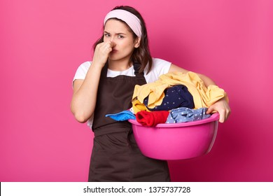 Brunette houseworker holding her nose with one hand, having full pink basin of bad smelling items of clothes, trying to bear smell. Emotional exhausted model poses isolated over pink background.