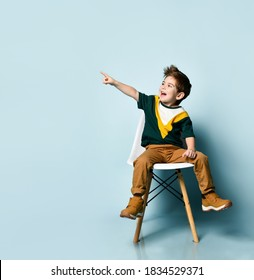 brunette kid in colorful t-shirt and brown pants. Smiling and pointing at something by forefinger, sitting on white chair against blue studio background. Childhood, fashion. Close up, copy space - Shutterstock ID 1834529371