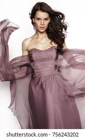 Brunette in a long dress posing