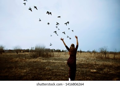 The brunette with long hair in a claret dress runs for birds across the field in the afternoon
