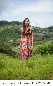 Brunette long hair East Asian girl with flower crown walking bare foot with background of green hills in Ranau, Sabah.