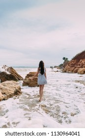 brunette with long hair stand in sea foam on the seashore/ girl in sea foam on the seashore. stony seashore