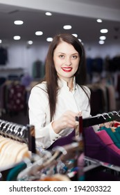 Brunette long-haired woman choosing clothes at clothing store