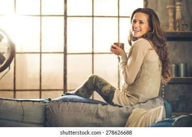 A brunette long-haired woman is seen from the side while sitting on the back of a sofa. She  is smiling and holding a hot cup of coffee. Industrial chic background, and cozy atmosphere.