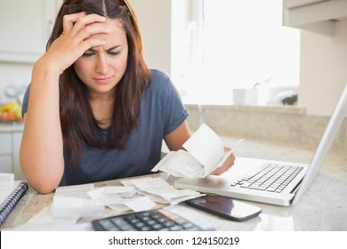 Brunette looking worried over bills in kitchen