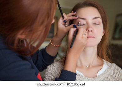 Brunette make up artist woman applying make up for a caucasian brunette bride, preparing her for a wedding photosession or a date