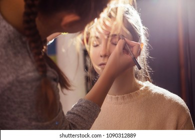 Brunette make up artist woman applying make up for a brunette bride in her wedding day. Making eyebrow correction
