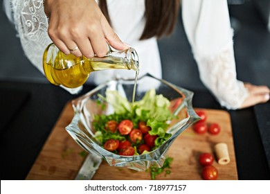 Brunette is making a salad adding olive oil on wooden cutting dowel