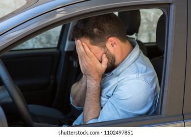 brunette man depressed and sad in a car