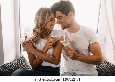 Brunette man embracing girlfriend and drinking champagne. Family couple celebrating anniversary.