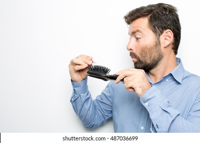 Brunette man finds his hair in the hairbrush